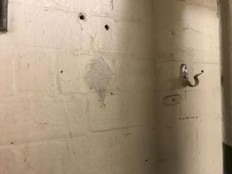 Asbestos insulation debris and snots stuck to walls and surfaces where pipes are present or have been in the past. Potentially painted over and hidden.